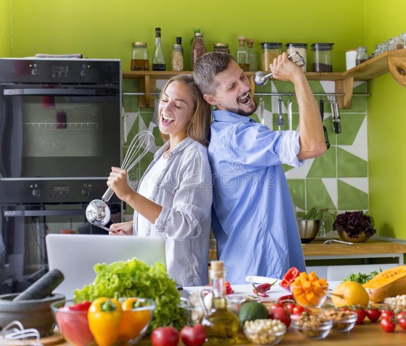 Young Couple of vegans singing and having fun near table royalty free stock photo