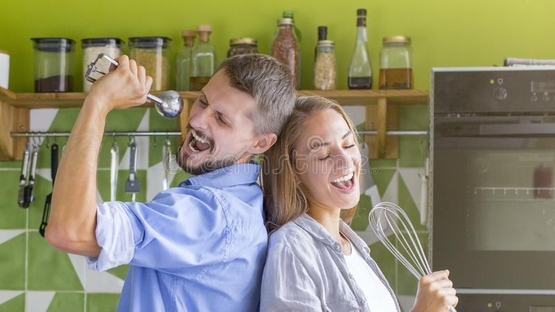 Young couple of vegetarians dancing and singing while cooking stock photo