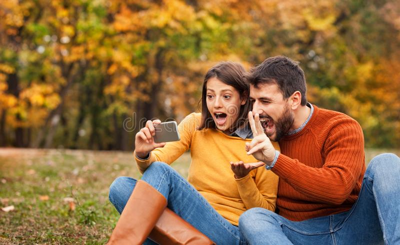 Young couple video chatting with their friends in the city park royalty free stock image