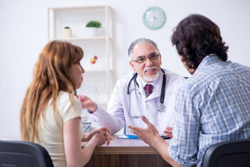 Young couple visiting old male doctor. The young couple visiting old male doctor stock image