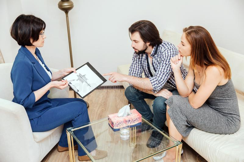 Young couple is visiting psychologist. They are sitting and looking at hand drawing very carefully. Doctor is explaining royalty free stock photography