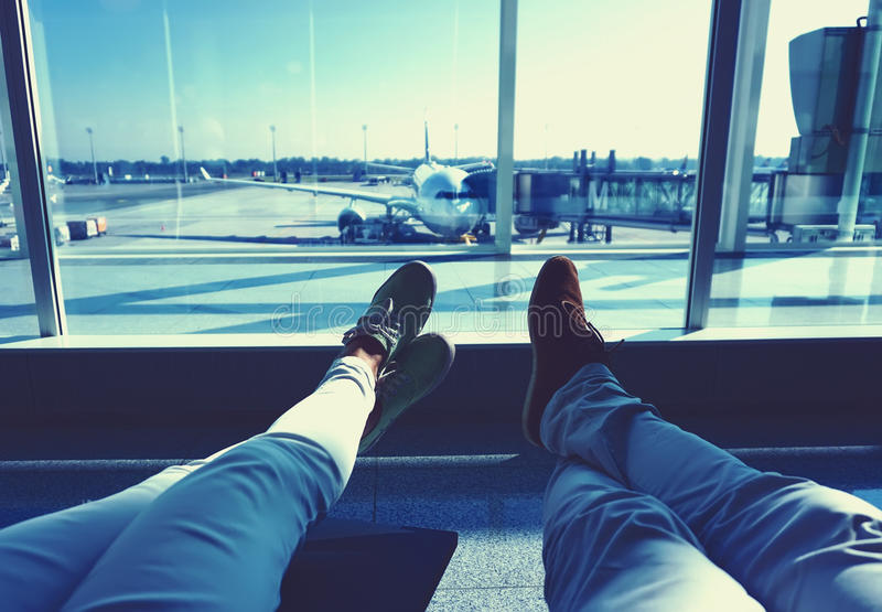 Young couple waiting for the plane at an airport. humans legs with the plane on the background. Travel concept Vintage colored picture stock photos
