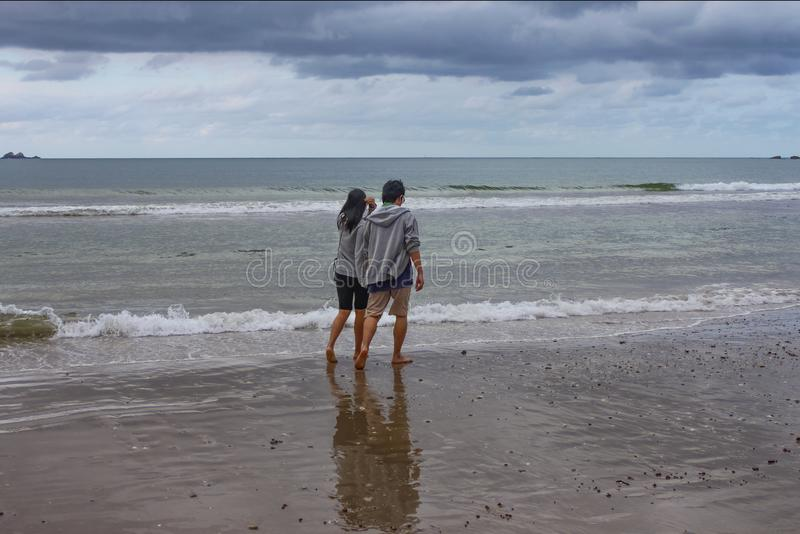 Young couple walk along the wet beach holding hands on a stormy day in Bryron Bay NSW Australia 8 29 2014. A young couple walk along the wet beach holding hands stock photography