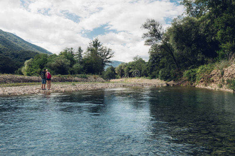 Young Couple Is Walking Along The River Summer, Together Concept Rear View stock photography