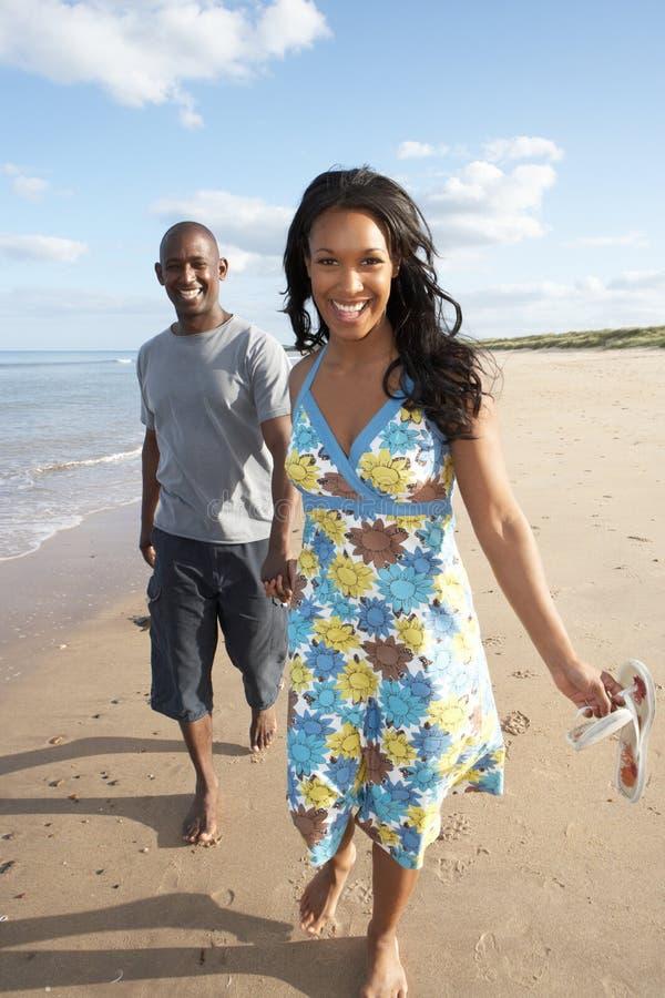 Download Young Couple Walking Along Shoreline Stock Photo - Image: 13672884