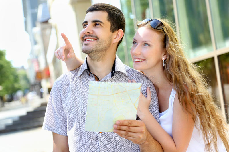 Young couple walking around the city. Holding a map stock image