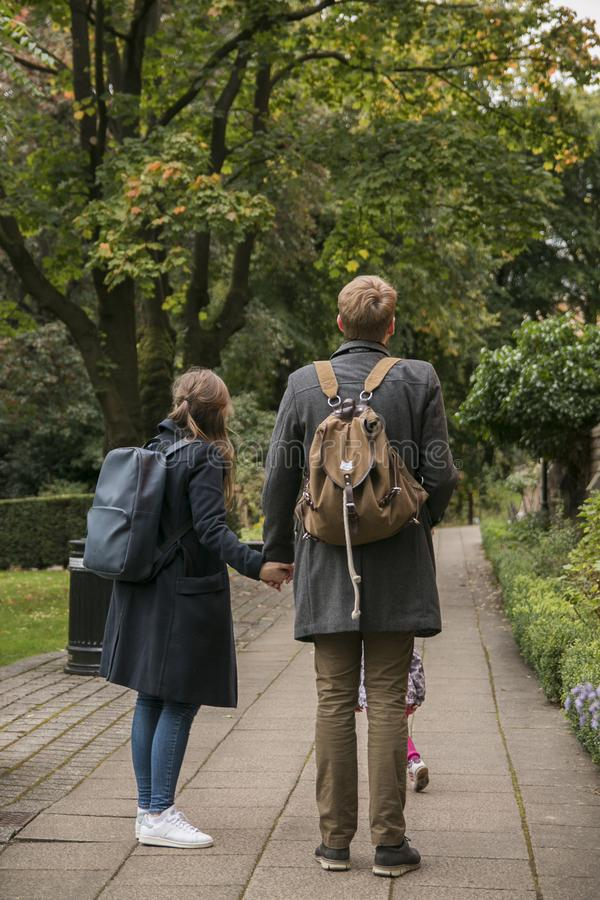Young couple walking with backpacks holding hands together stock image