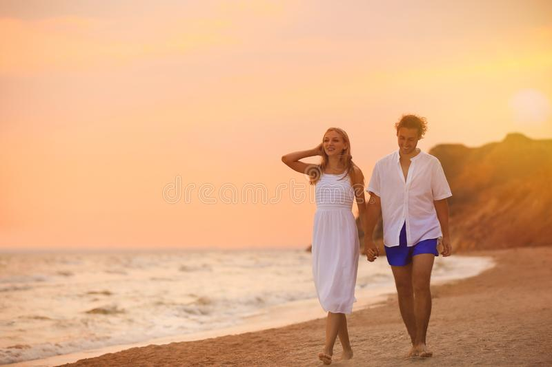 Young couple walking on beach stock photography