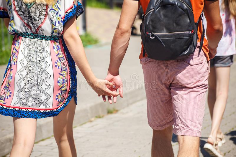 Young couple walking down the street holding hands stock photo