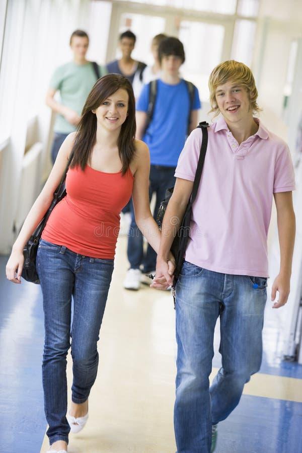 Young couple walking down university corridor stock photos