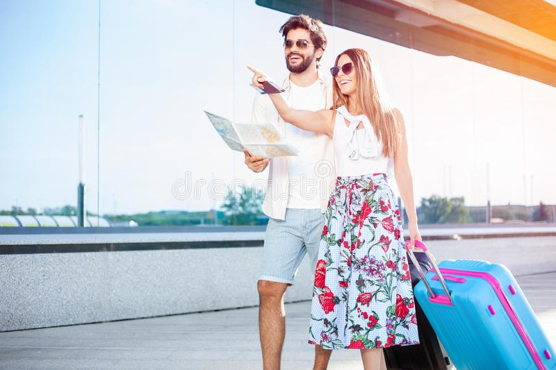 Young couple walking in front of an airport terminal building, pulling suitcases. Beautiful young couple walking in front of an airport terminal building stock image