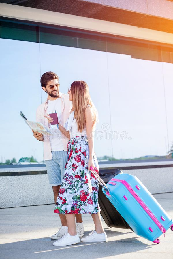 Young couple walking in front of an airport terminal building, pulling suitcases royalty free stock images