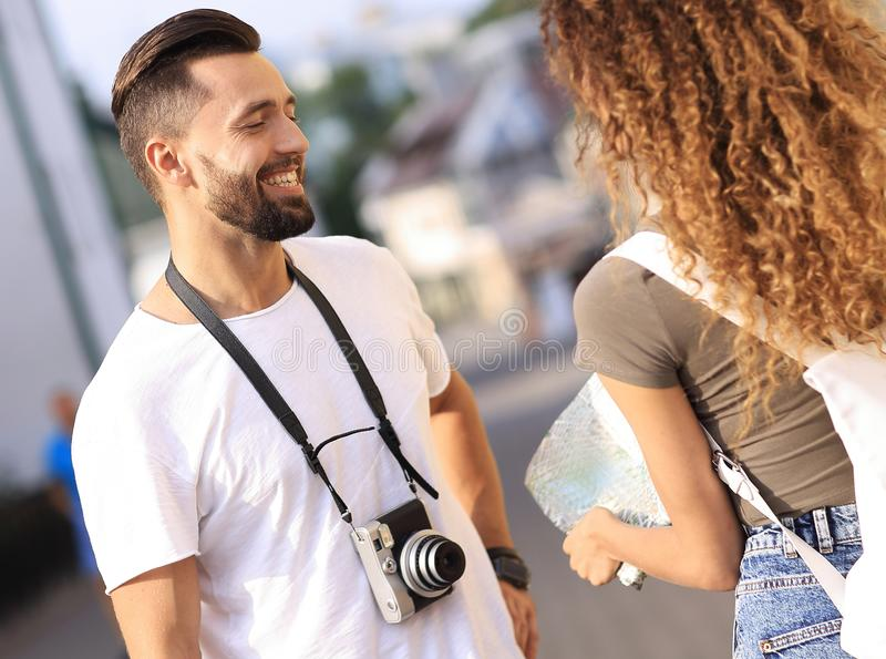 Young couple walking and looking at a guide while looking happy. Couple of loving tourists enjoying city tour royalty free stock photos