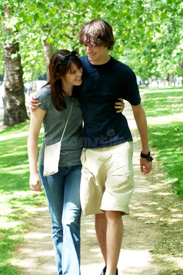 Young couple walking in park. A teenage couple arms around each other walking in the park in summer