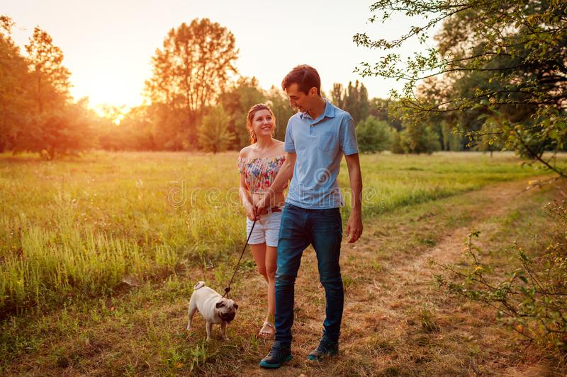 Young couple walking pug dog in autumn forest. Happy puppy running along and having fun playing with master. stock photos