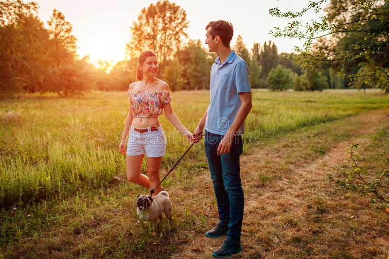 Young couple walking pug dog in autumn forest. Happy puppy running along and having fun playing with master. royalty free stock photo