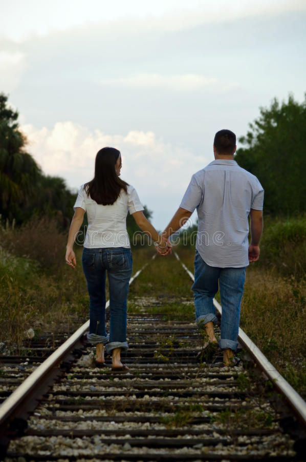 Download Young Couple Walking On Rail Tracks Stock Photo - Image: 15764482