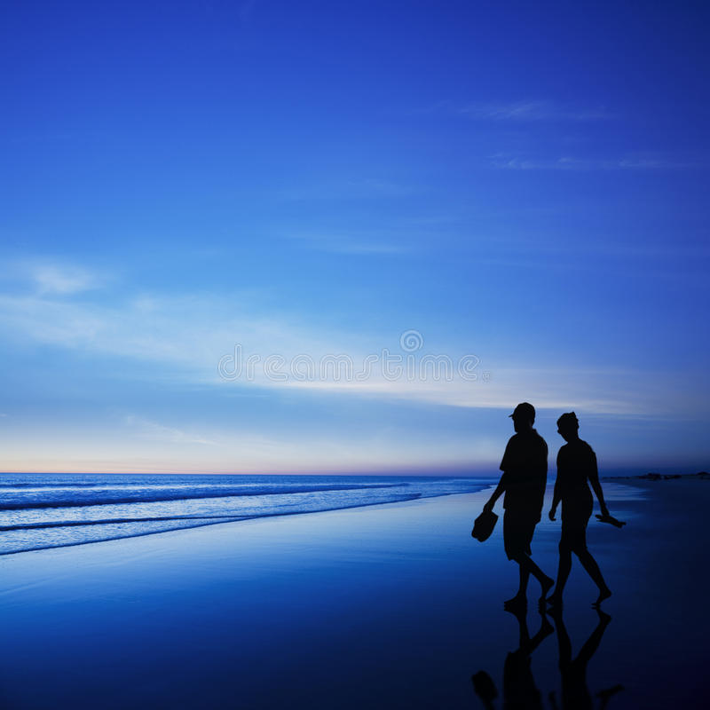 Young Couple Walking On Romantic Beach At Twilight Stock