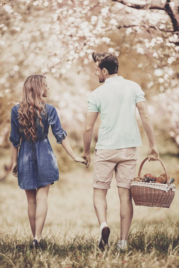 Young Couple Walking in Summer Park on Sunny Day. stock photo
