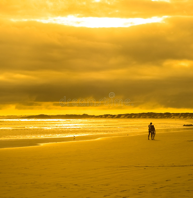 Young couple walking in sunset beach royalty free stock image