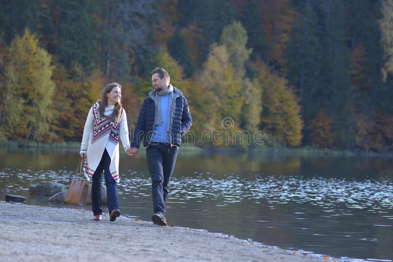 Young couple walking together on a beach and holding hands royalty free stock photos
