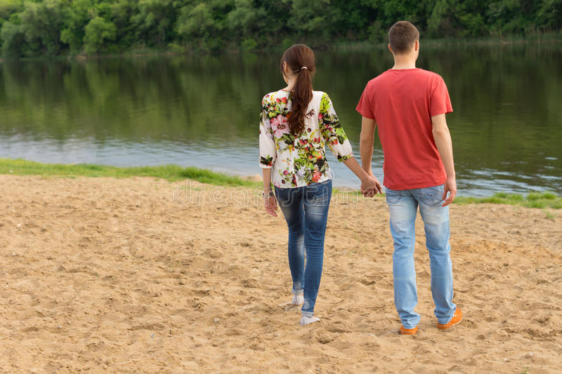 Young couple walking towards the edge of the lake royalty free stock photos