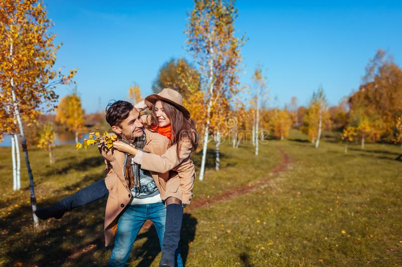 Young couple walks in autumn forest. Man giving his girlfriend piggyback. People having fun stock photo