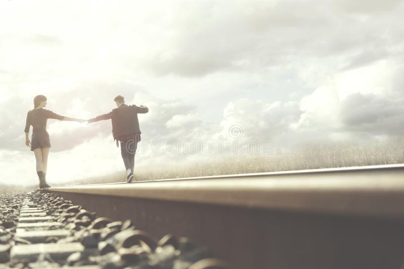 Young couple walks hand in hand on rails in a surreal place royalty free stock photos
