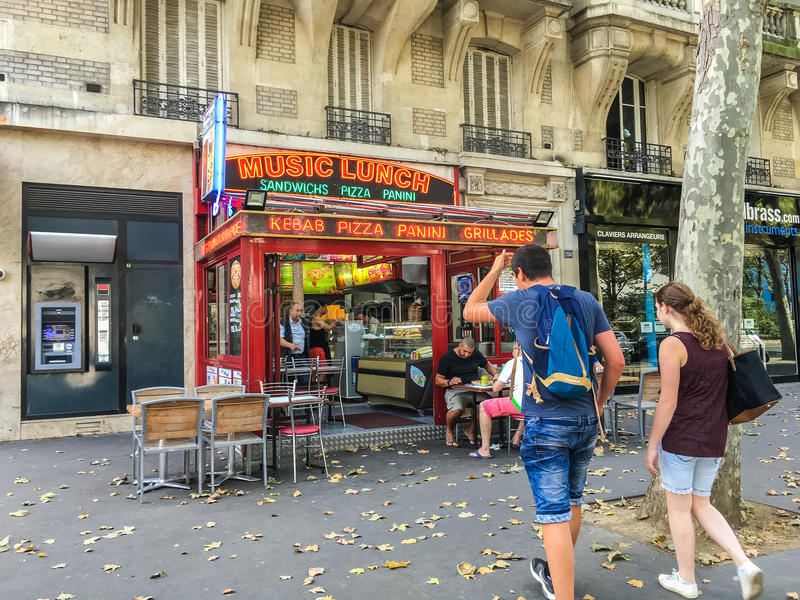 Young couple walks toward sandwich shop in Paris royalty free stock image