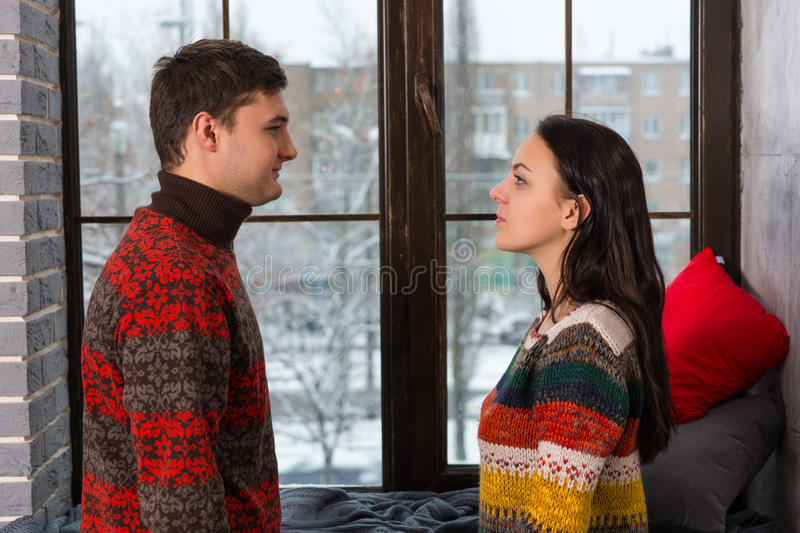 Young couple in warm knitted sweaters looking at each other while standing near windowsill. With pillows and blanket royalty free stock images