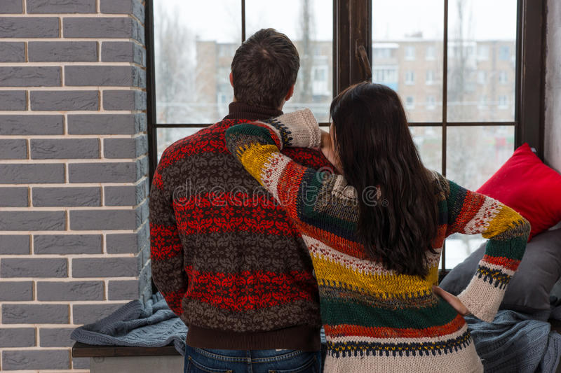 Young couple in warm knitted sweaters looking out the window while standing near windowsill. With pillows and blanket stock photo