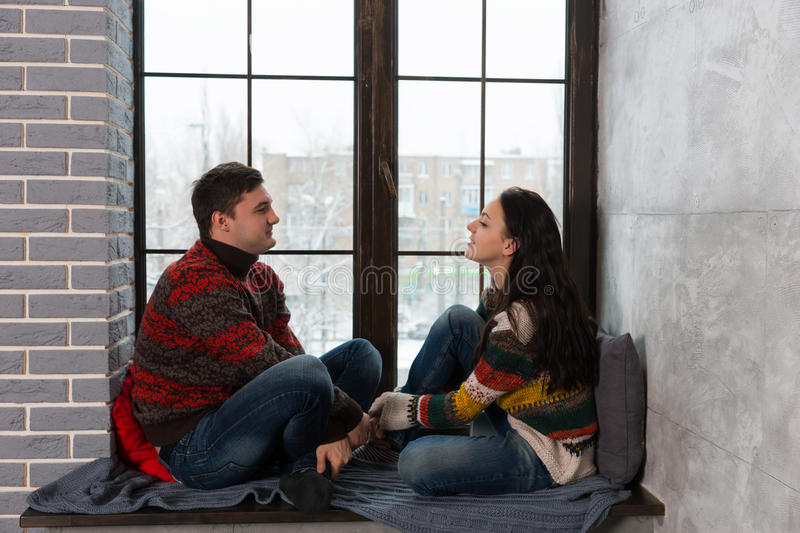 Young couple in warm knitted sweaters talking while sitting on t. He windowsill with pillows and blanket stock image