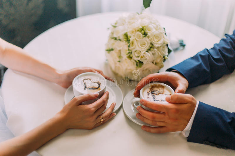 Young couple warming their hands by coffee cups at the table in cafe. Bouquet of beautiful white flowers on background royalty free stock image