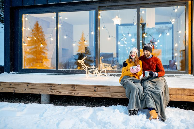 Couple warming up near the house during the winter holidays. Young couple warming up with plaid and hot drinks sitting on the terrace of the modern house in the royalty free stock image