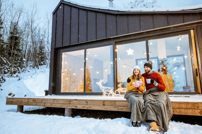 Couple warming up near the house during the winter holidays. Young couple warming up with plaid and hot drinks sitting on the terrace of the modern house in the stock images