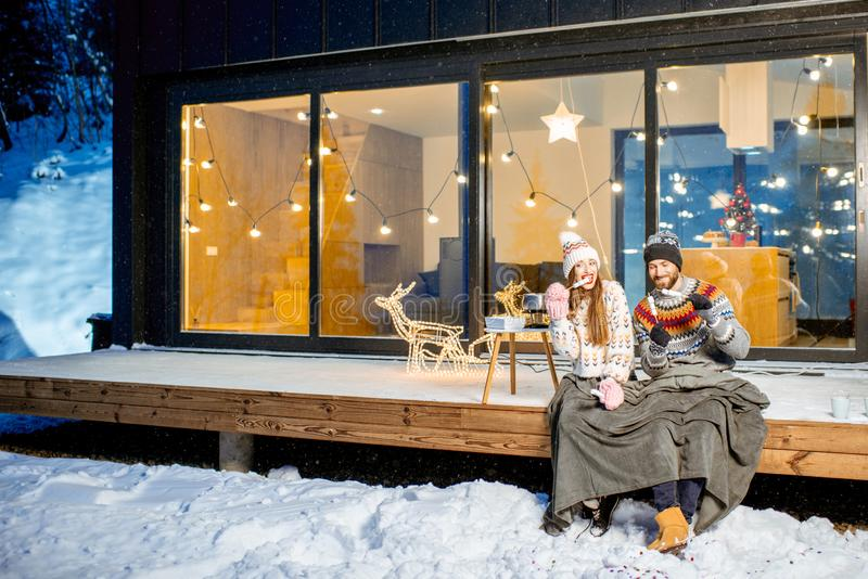 Couple warming up near the house during the winter holidays. Young couple warming up with plaid and marshmallow sitting on the terrace of the modern house in the stock images