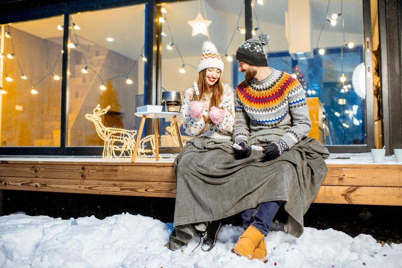 Couple warming up near the house during the winter holidays. Young couple warming up with plaid and marshmallow sitting on the terrace of the modern house in the stock photos