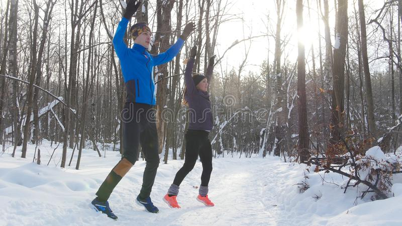 Young couple warming up in winter forest stock photos