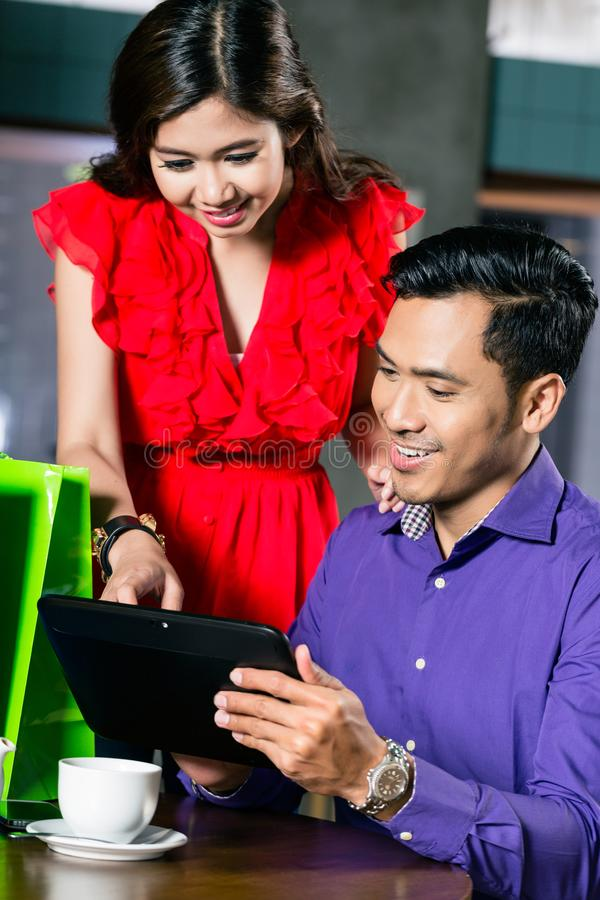 Young couple watching a funny video on a tablet connected to the internet royalty free stock photo