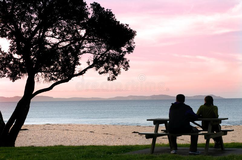 Young couple watching the sunset. Silhouette of young couple sitting on a bench near the ocean and watching the sunset royalty free stock photo