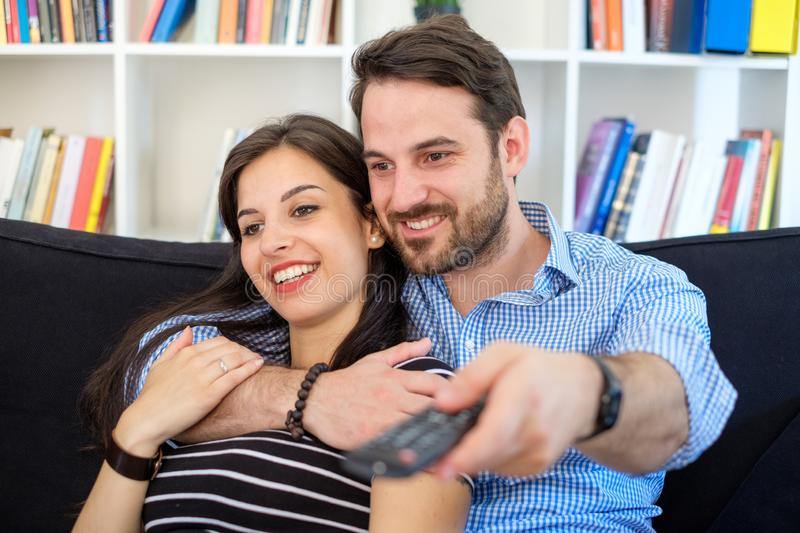 Young couple watching tv at home and having fun stock photography