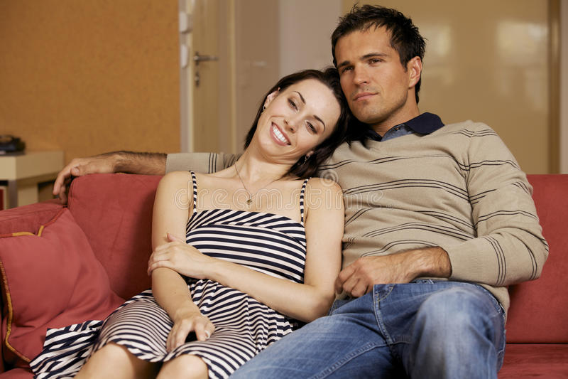 Young couple watching TV in hotel room royalty free stock image
