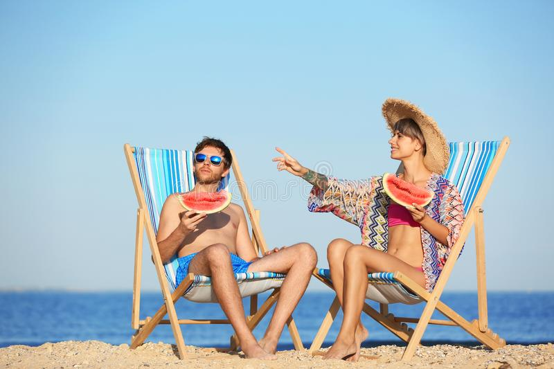 Young couple with watermelon slices in beach chairs. At seacoast stock image