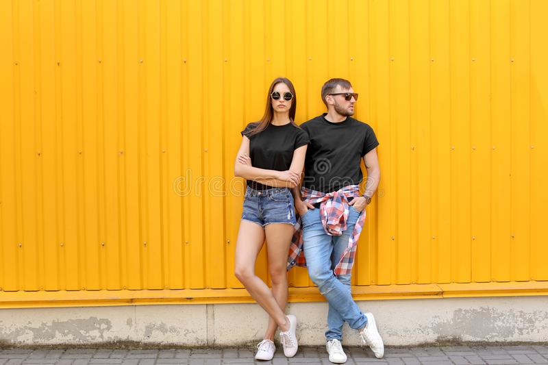 Young couple wearing black t-shirts near color wall stock image