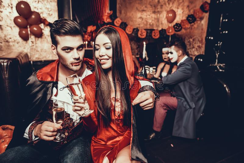 Young Couple Wearing Costumes Drinking Champagne stock images