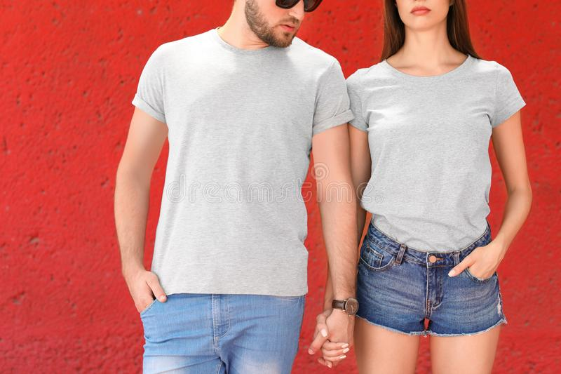 Young couple wearing gray t-shirts near color wall stock photo