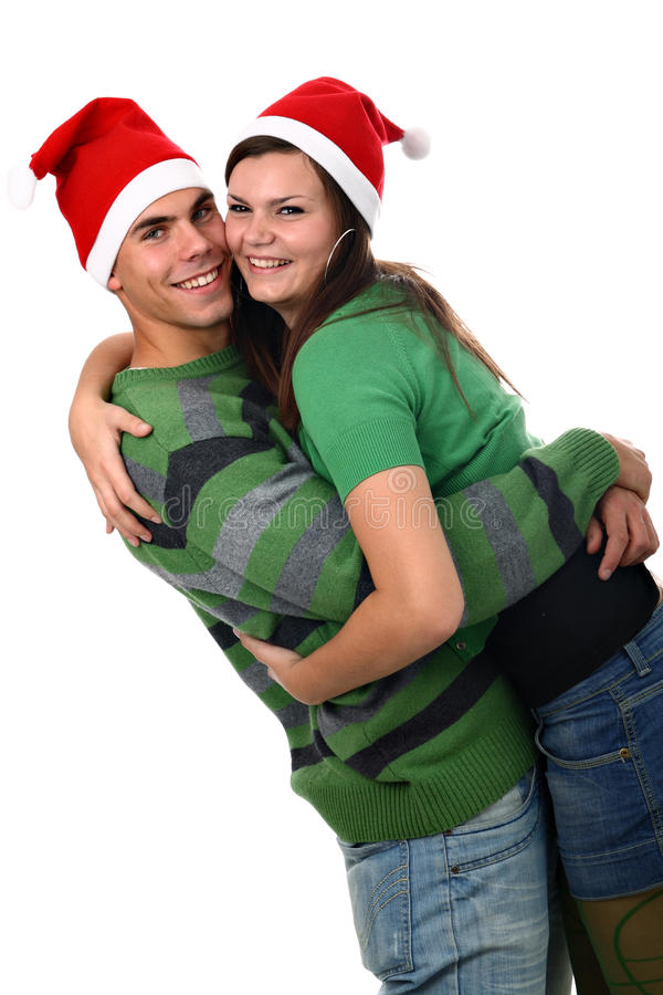 Young couple wearing Santa hats hugging each other