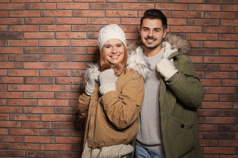 Young couple wearing warm clothes against wall, space for text. Ready for winter vacation. Young couple wearing warm clothes against brick wall, space for text royalty free stock image