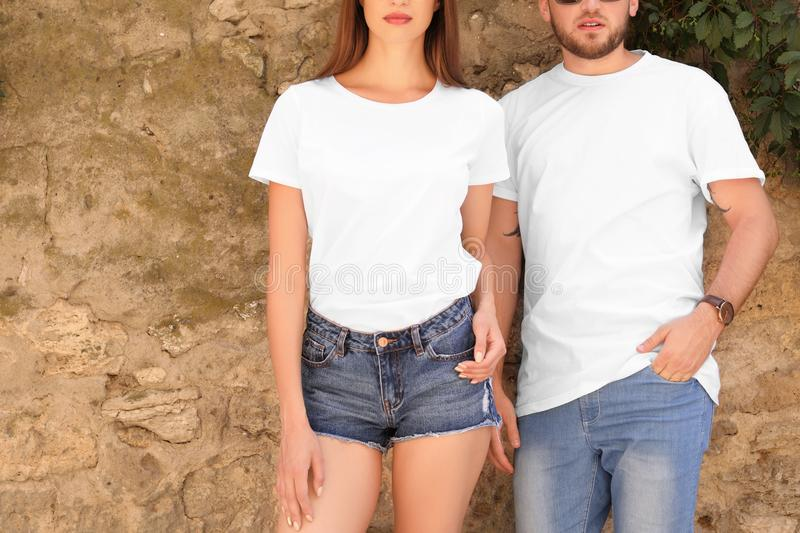 Young couple wearing white t-shirts near stone wall royalty free stock photo