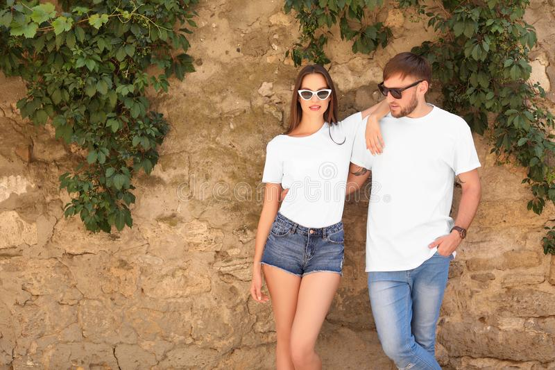 Young couple wearing white t-shirts near stone wall stock photos